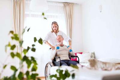 caregiver assisting senior man in therapy
