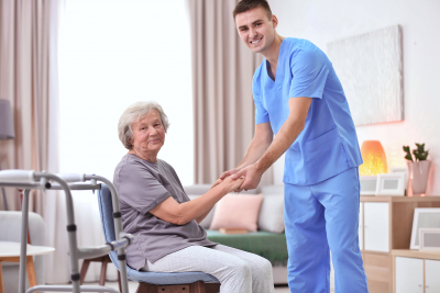 caregiver holding the hands of senior woman