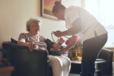 caregiver checking the blood pressure of the old woman